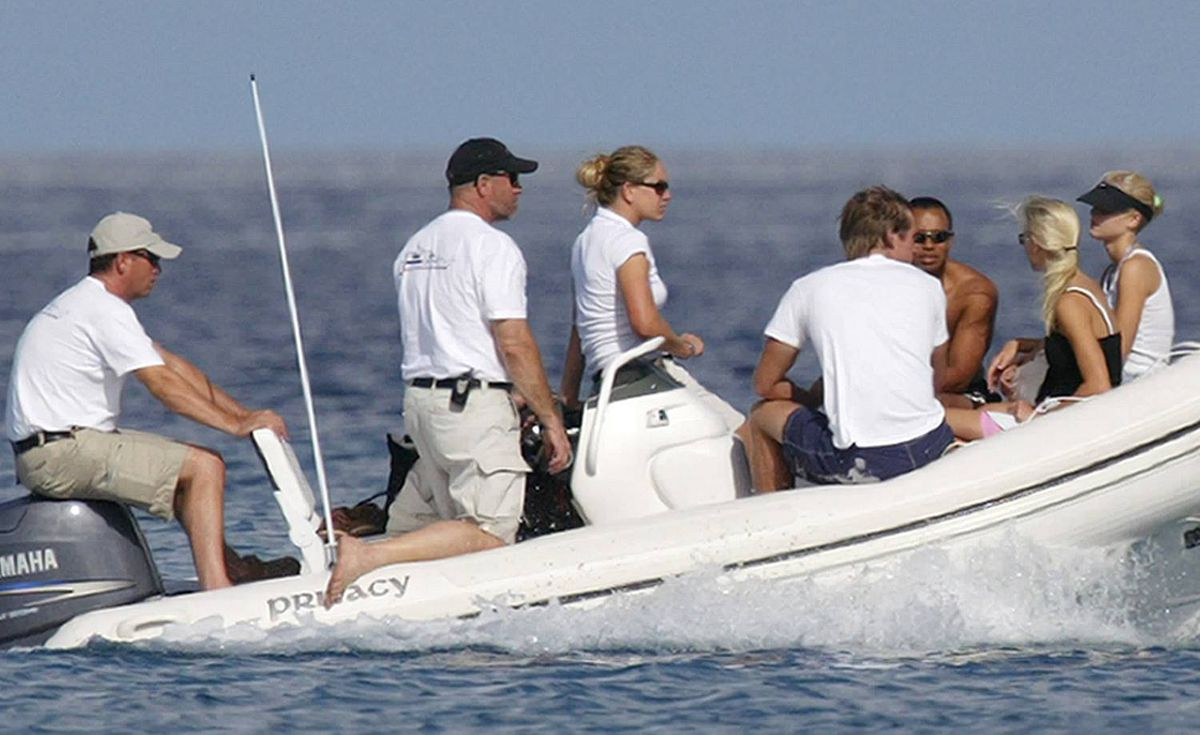 "Tiger Woods sits in a small dive boat along with his new bride Elin Nordegren, in black bathing suit, and her twin sister, Josephin, wearing visor, off the beach of the luxury resort Sandy Lane in Barbados on Oct. 6, 2004. The group made its way to shore from Woods's luxury yacht named ""Privacy""."