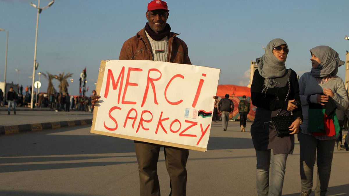 """Libyan women walk past a man holding a placard reading in French """"Thank you Sarkozy"""" in a street of Benghazi on March 24, 2011, as rebels battled on to the eastern oil town of Ajdabiya."""