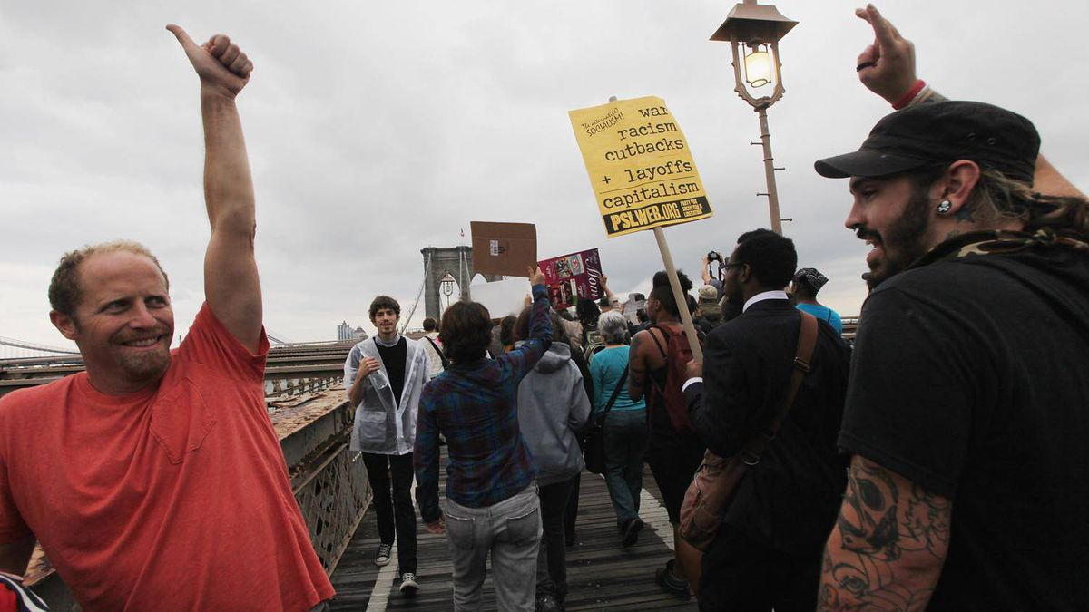 A passing pedestrian salutes the Occupy Wall Street protesters along the Brooklyn Bridge on Oct. 1, 2011.