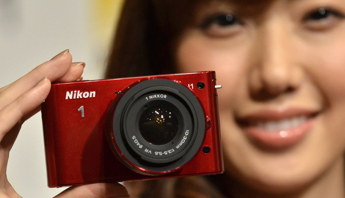 "A model displays a ""Nikon 1 J1"" interchangeable lens camera in Tokyo on September 21, 2011. Nikon unveiled two models of its new compact camera equipped with a 1-inch sized CMOS image sensor a focusing unit with 73 focus points, and four new lenses."