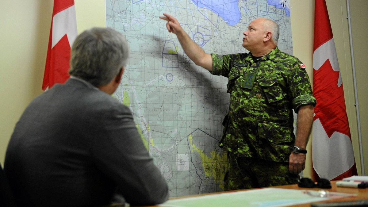 Prime Minister Stephen Harper is given a technical briefing by General Charles Bouchard prior to delivering a speech at Camp Fortin on the Trapani-Birgi Air Force Base in Trapani, Italy, on Thursday, Sept. 1, 2011.