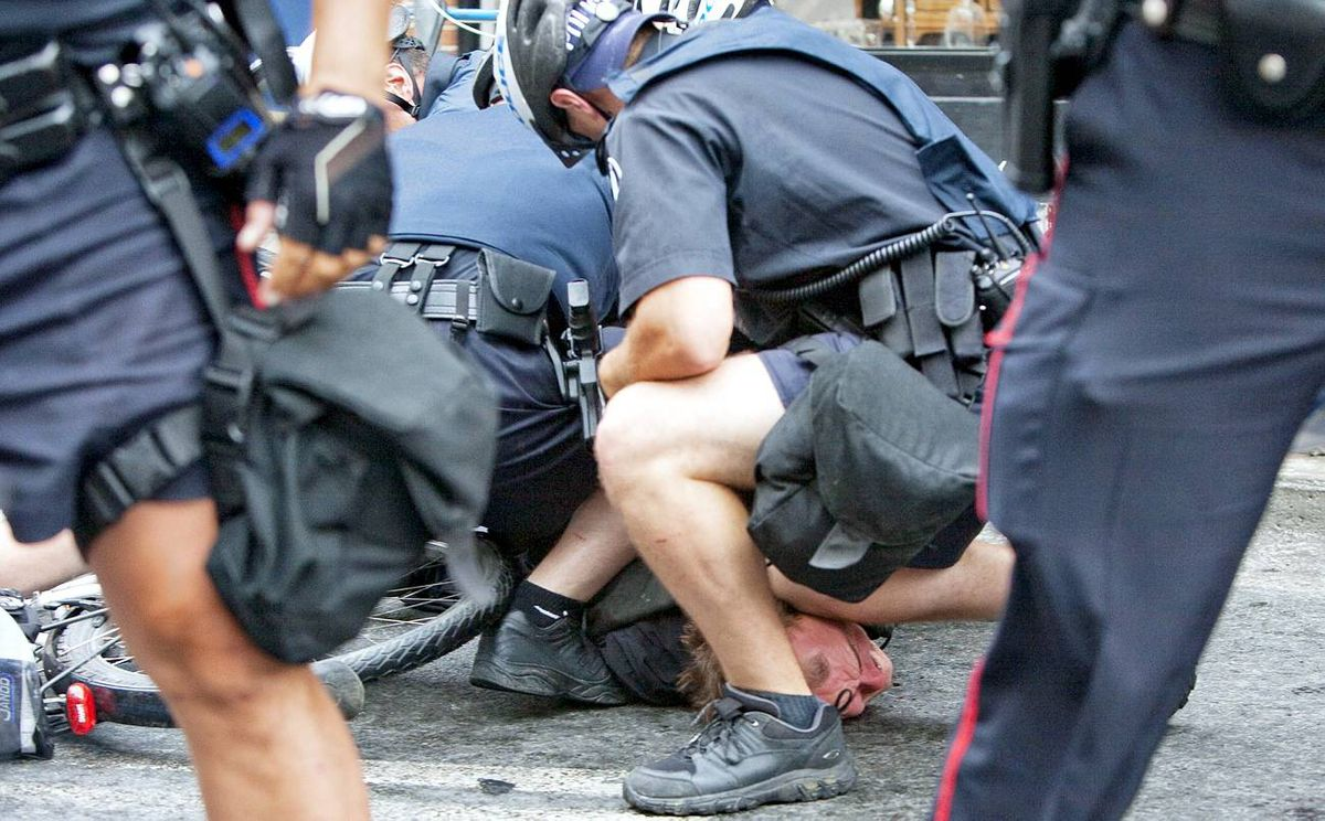 A protester is taken to the ground by police in Yorkville during demonstrations against the G20/G8 Summit in Toronto.