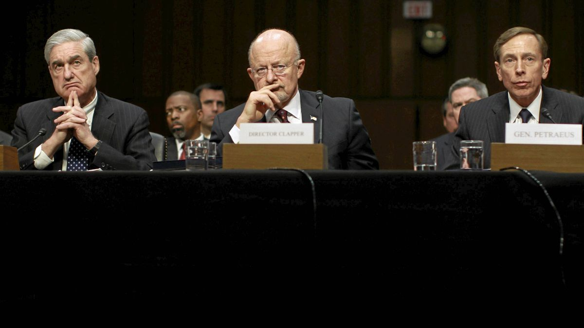 """Director of National Intelligence James Clapper, centre, listens along with FBI Director Robert Mueller, left, and CIA Director David Petraeus as they testify before a Senate (Select) Intelligence hearing on """"World Wide Threats"""" on Capitol Hill in Washington Jan. 31, 2012."""