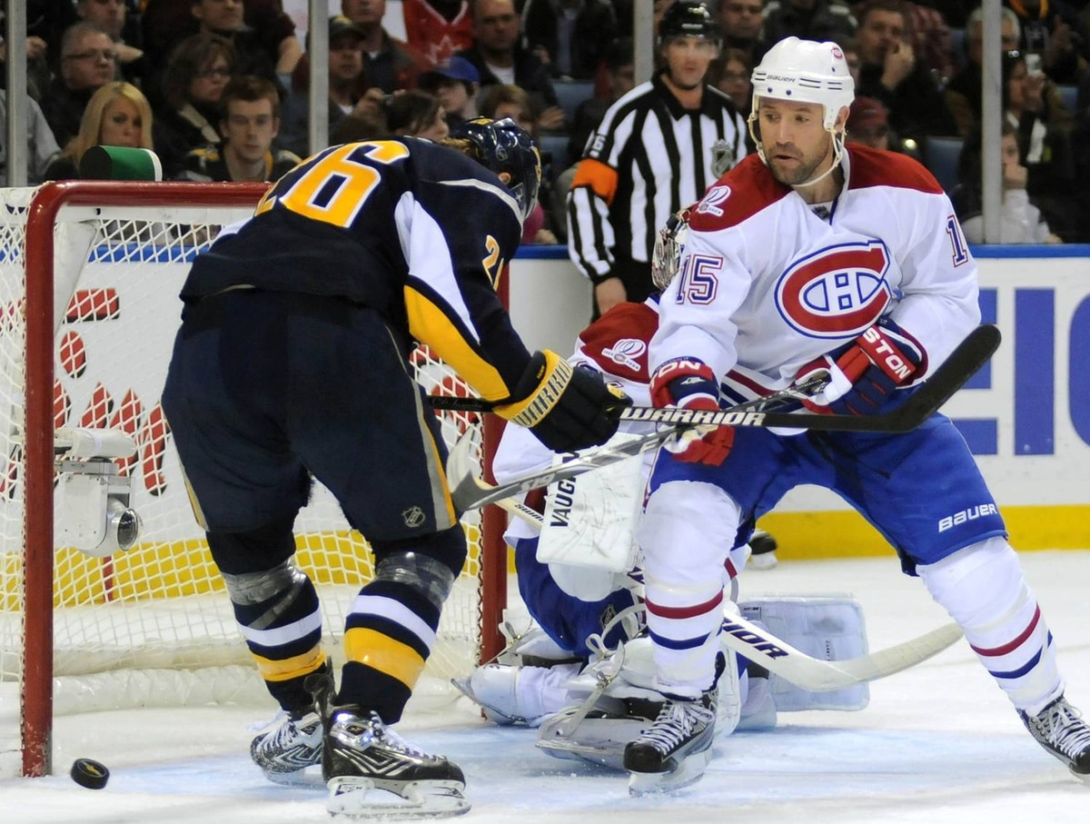 Buffalo Sabres left winger Thomas Vanek (L) misses the puck during a scoring chance in front of the Canadiens goal as Montreal center Glen Metropolit (R) closes during second period NHL hockey action in Buffalo, New York, March 24, 2010. REUTERS/Gary Wiepert