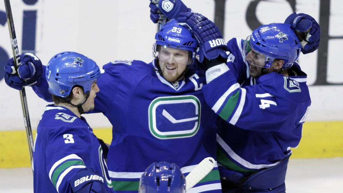 Vancouver Canucks' Henrik Sedin, centre, celebrates his goal against the Edmonton Oilers with teammates Kevin Bieksa, left, and Alex Burrows during the second period of their NHL hockey game in Vancouver on Saturday.