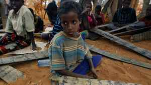 Young Somali refugees hold their prayer tablets as they attend koranic studies at an outdoor madrasa at the Ifo camp outside Dadaab, Eastern Kenya, 100 kms (60 miles) from the Somali border, Tuesday Aug. 9, 2011.