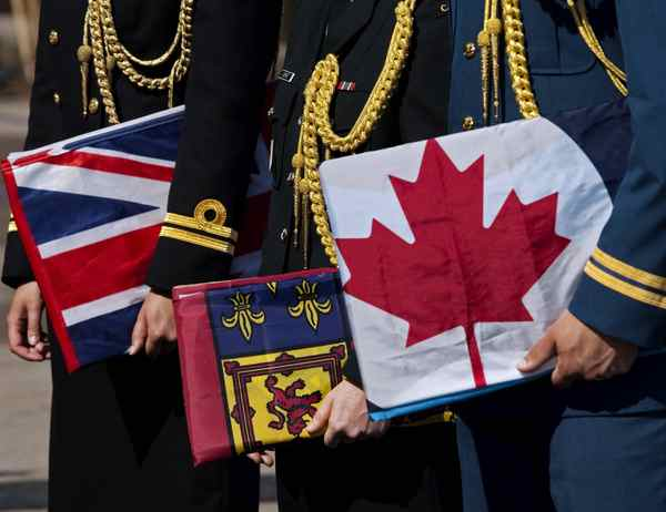 Navy, army and air force officers, left to right, hold flags of the three forces at a ceremony in Halifax on Tuesday, Aug. 16, 2011.
