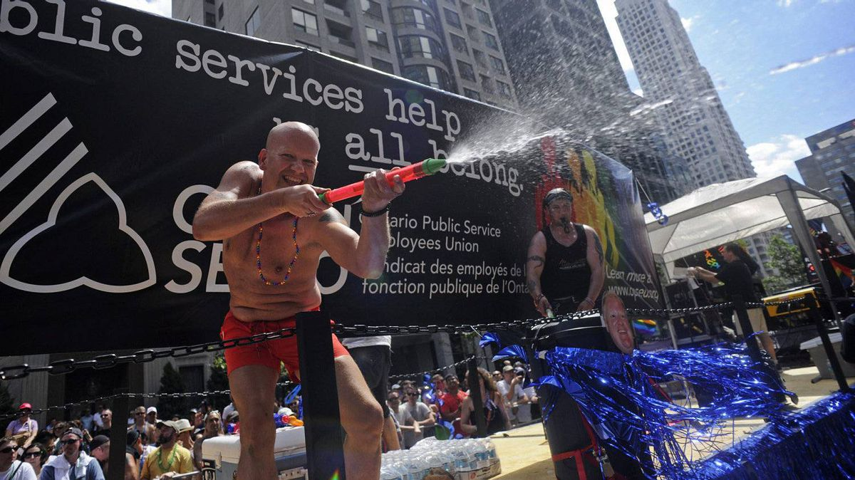 People aboard a float for the Ontario Public Service Employees Union spray onlookers with water. Temperatures went as high as 35 C Sunday with partly cloudy skies.