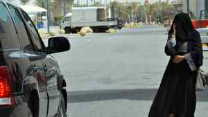 A Saudi woman talks on the phone while walking in Riyadh on June 14, 2011.