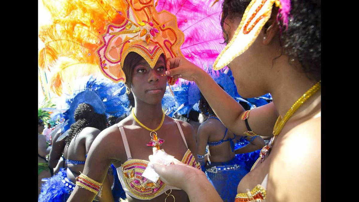 Participants of the Caribbean Carnival put the finishing touches on their costumes.