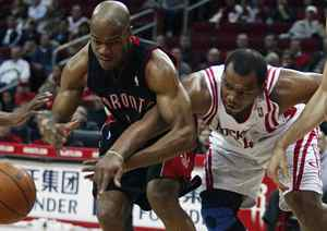 Houston Rockets forward Chuck Hayes, right, and Toronto Raptors guard Jarrett Jack, left, get tangled up as they struggle for a loose ball during the first half of their NBA basketball game in Houston March 1, 2010.