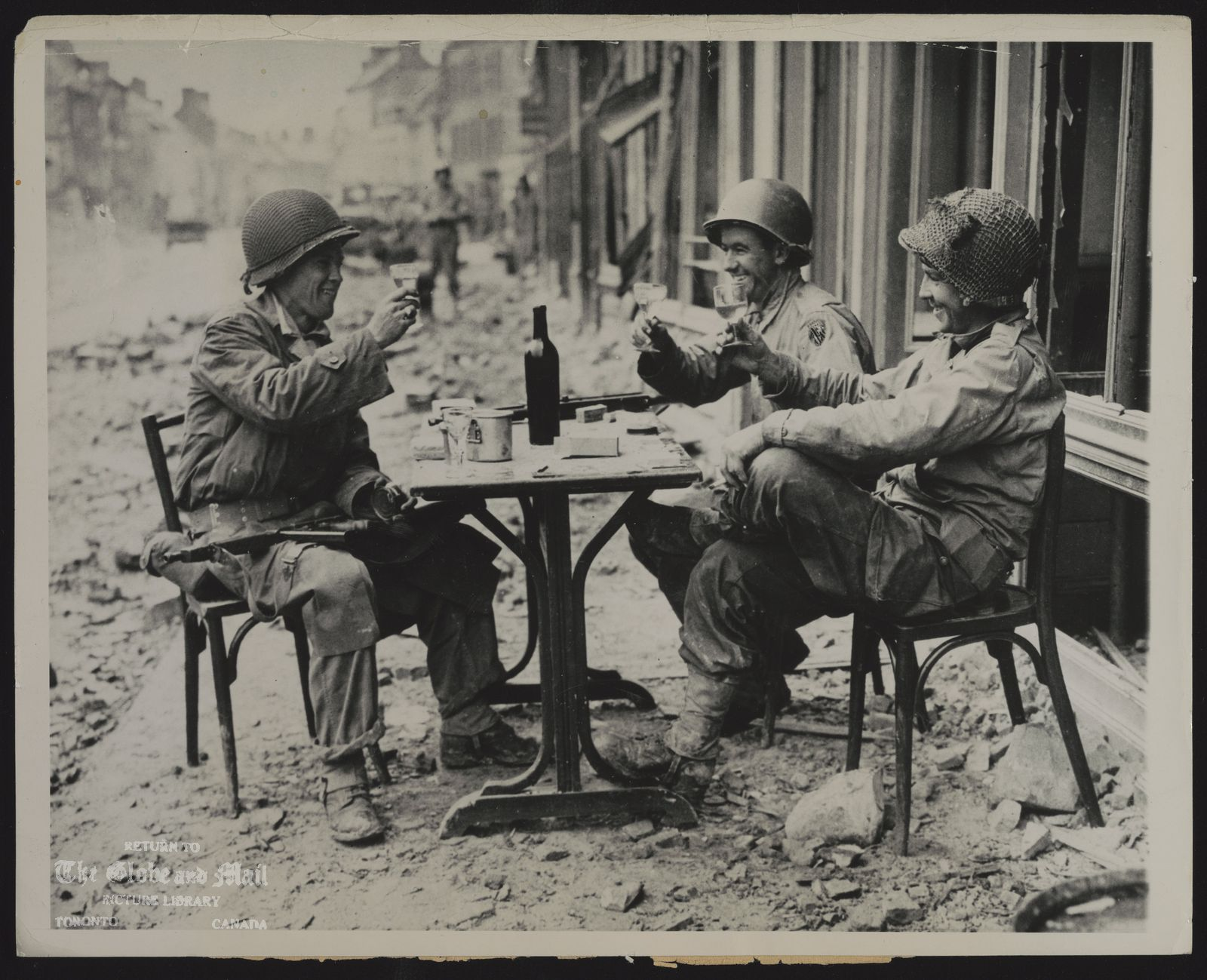 The notes transcribed from the back of this photograph are as follows: WORLD WAR II France TO VICTORY -- A YANK VERSION OF A SIDEWALK CAFE, IN FALLEN LA HAVE DU PUITS, FRANCE, AS ROBERT McCURDY (LEFT) NEWARK, N.J., SGT. HAROLD SMITH, BRUSH CREEK, TENN. (CENTRE), AND SGT RICHARD BENNETT, WILKES BARRE, PA, RAISE THEIR GLASSES IN A TOAST. ASSOCIATED PRESS PHOTO 7-15-44 [1944]