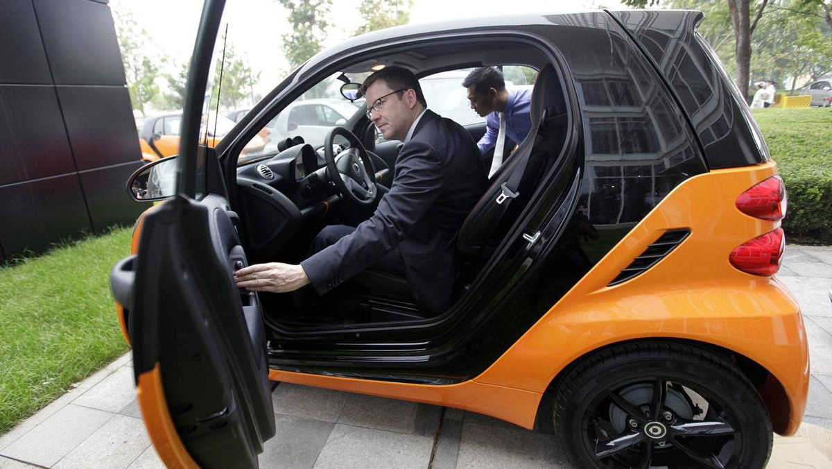 Mercedes-Benz China President and CEO Klaus Maier adjusts the car window of a Smart car during an interview with Reuters in Beijing July 14, 2011.