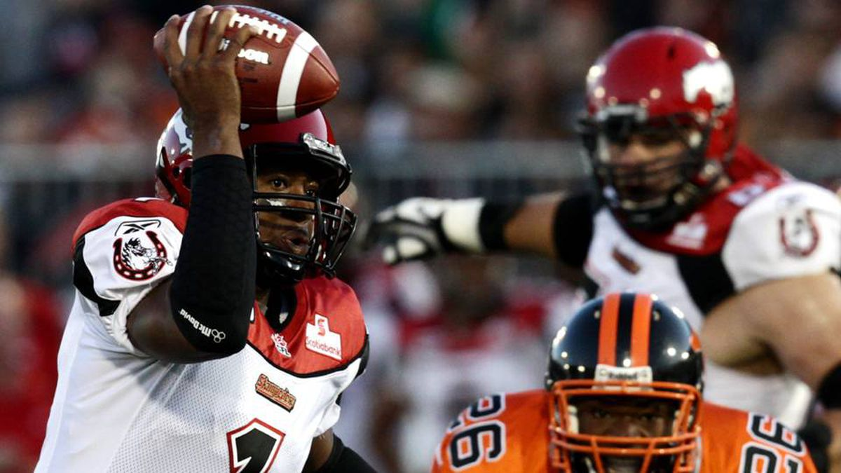 Calgary Stampeders' Henry Burris, left, rushes for a touchdown as B.C. Lions' Anthony Reddick chases after him during first half CFL action in Vancouver, B.C., on Friday August 27, 2010.