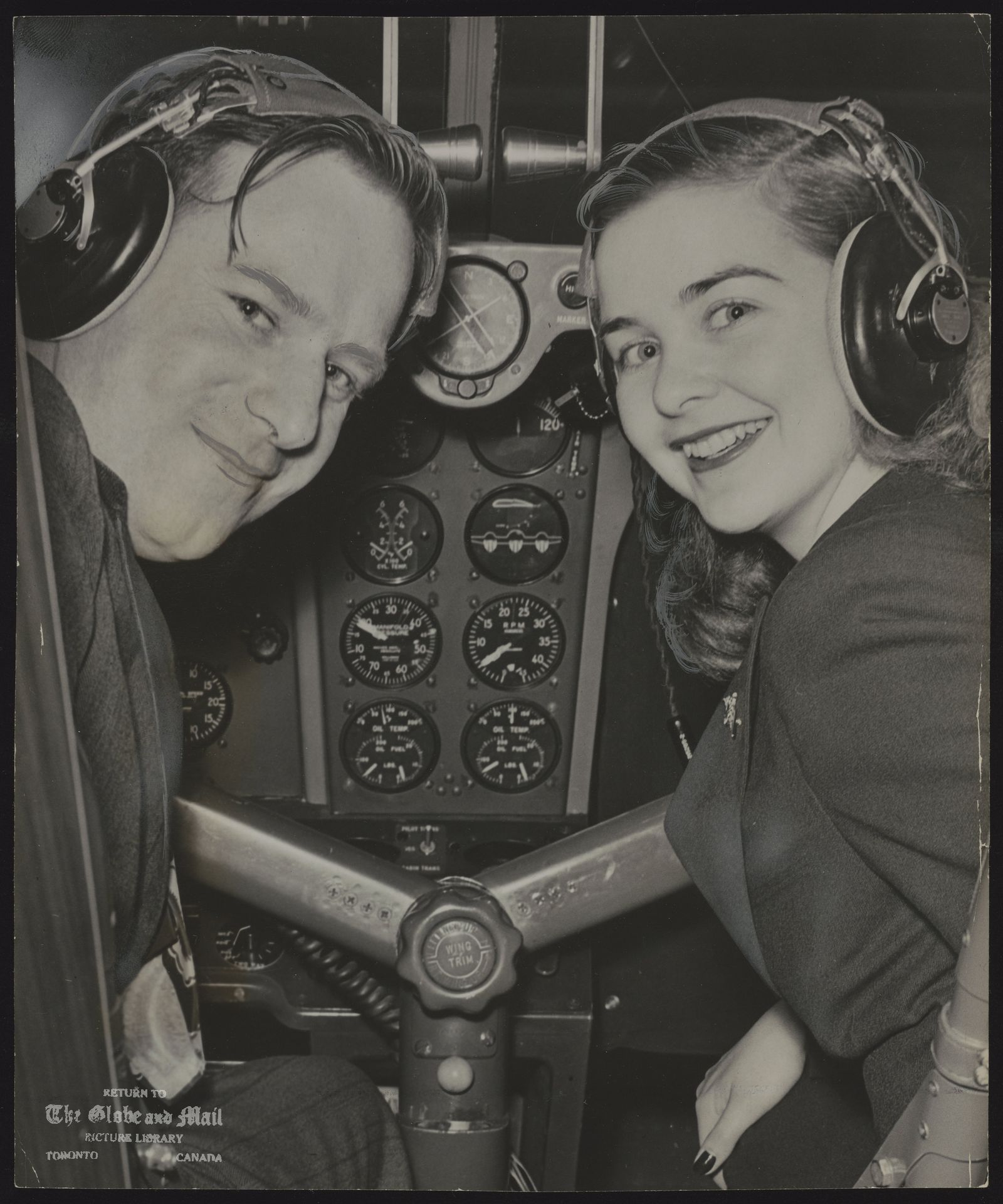 Through she hasn't received her private pilot's license yet, Barbara Ann Scott, [ladies world champion] centre of an Olympic Games controversy, had done enough flying to know what it was all about when she sat in the co-polot's seat of The Globe and Mail plane yesterday. with her is pilot Bill poag.