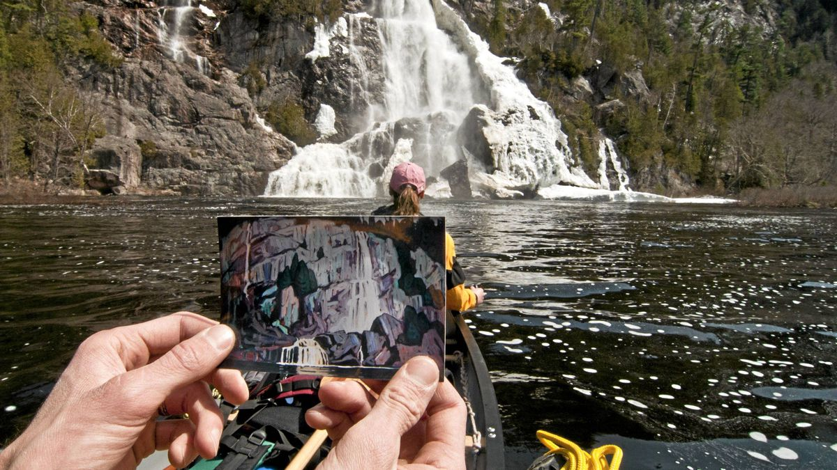 Writer Conor Mihell holds a small print of Algoma Waterfall – a painting of Bridal Veil Falls by J.E.H. MacDonald – in front of the real falls on the Agawa River.