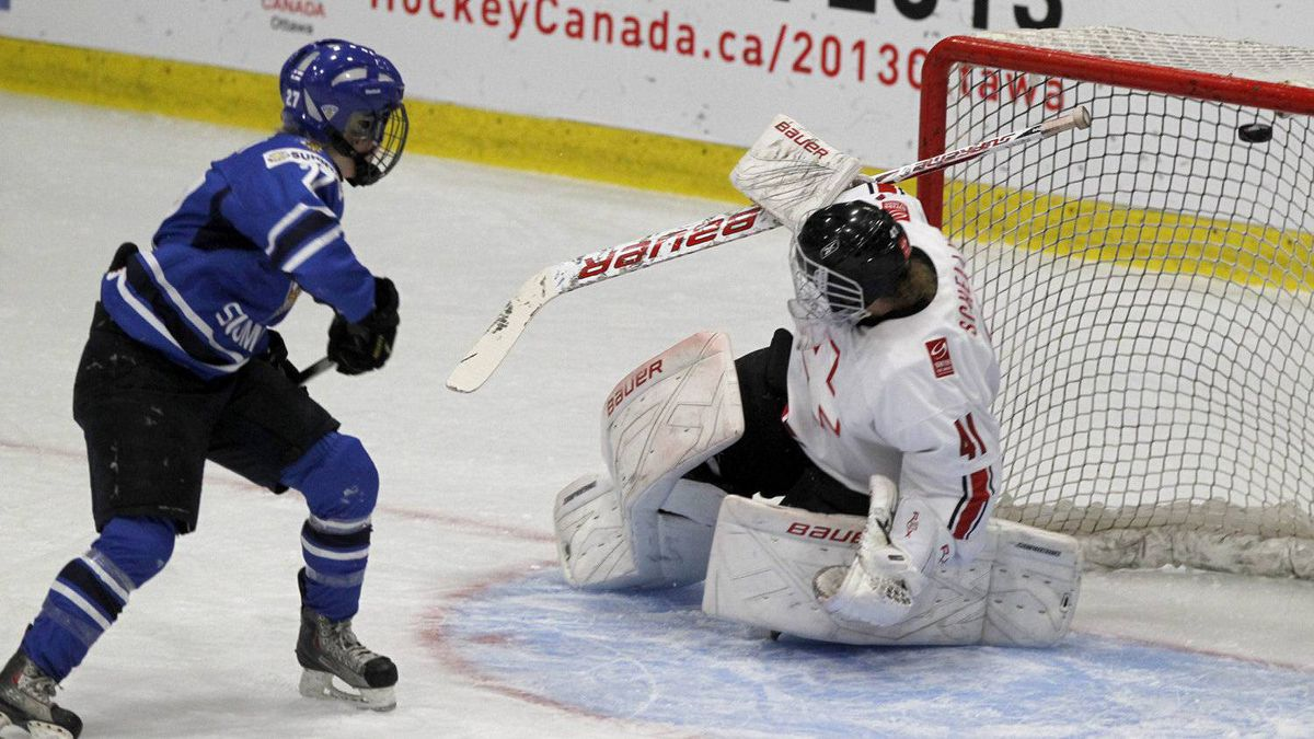 Finland forward Anne Helin (27) scores a goal on Switzerland goalie Florence Schelling during the bronze medal game of the World Women's Ice Hockey Championships Saturday, April 14, 2012 in Burlington, Vt.