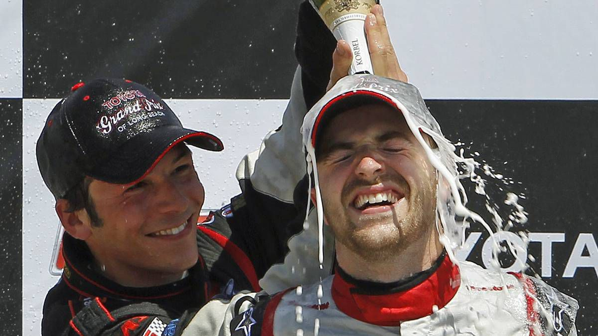 IRL driver James Hinchcliffe, right, is drench with champagne by third place finisher J.K. Vernay of France after Hinchcliffe won the IRL Firestone Indy LIghts auto race, Sunday, April 18, 2010, in Long Beach, Calif.