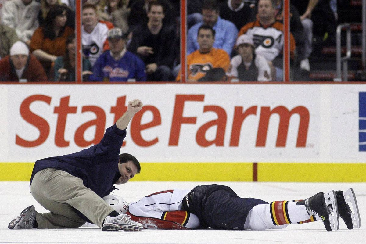 A trainer signals for a doctor while tending to Florida Panthers forward David Booth, who was blindsided by Mike Richards of the Philadelphia Flyers in an Oct. 24 game.