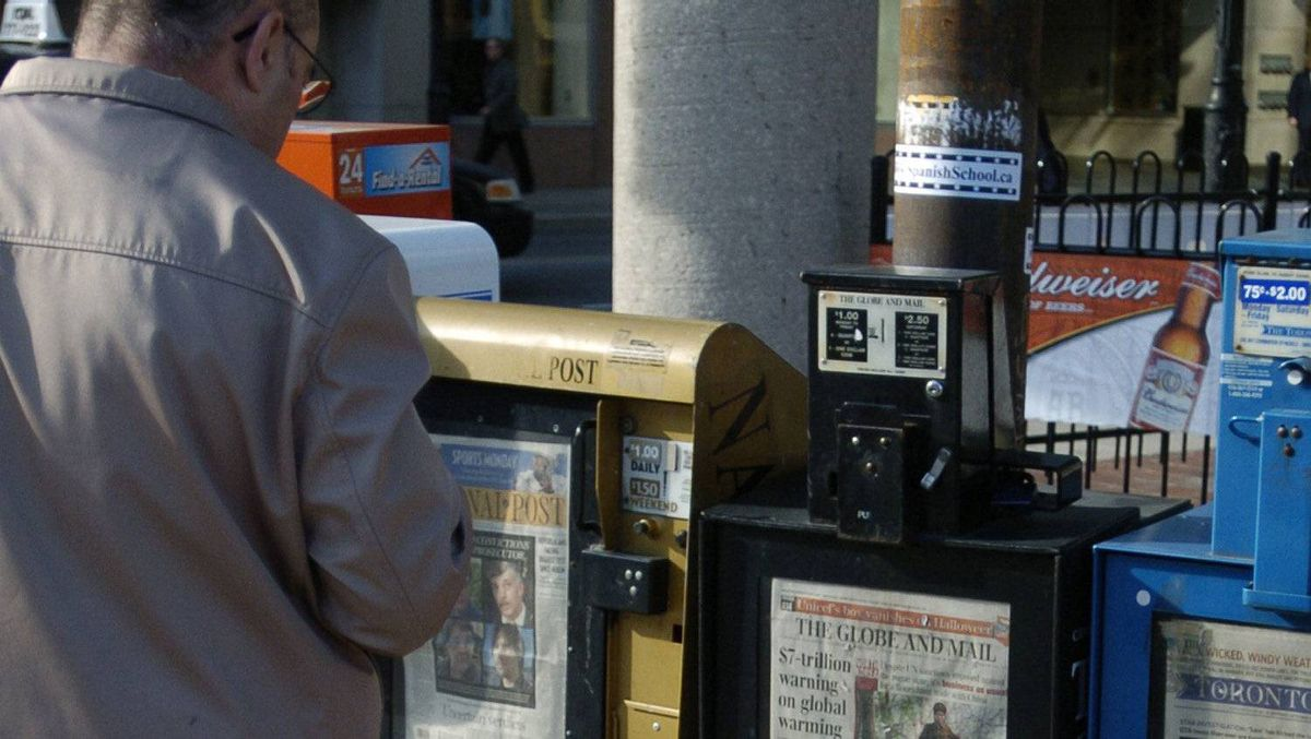 Pedestrians pass newspaper boxes in Toronto.