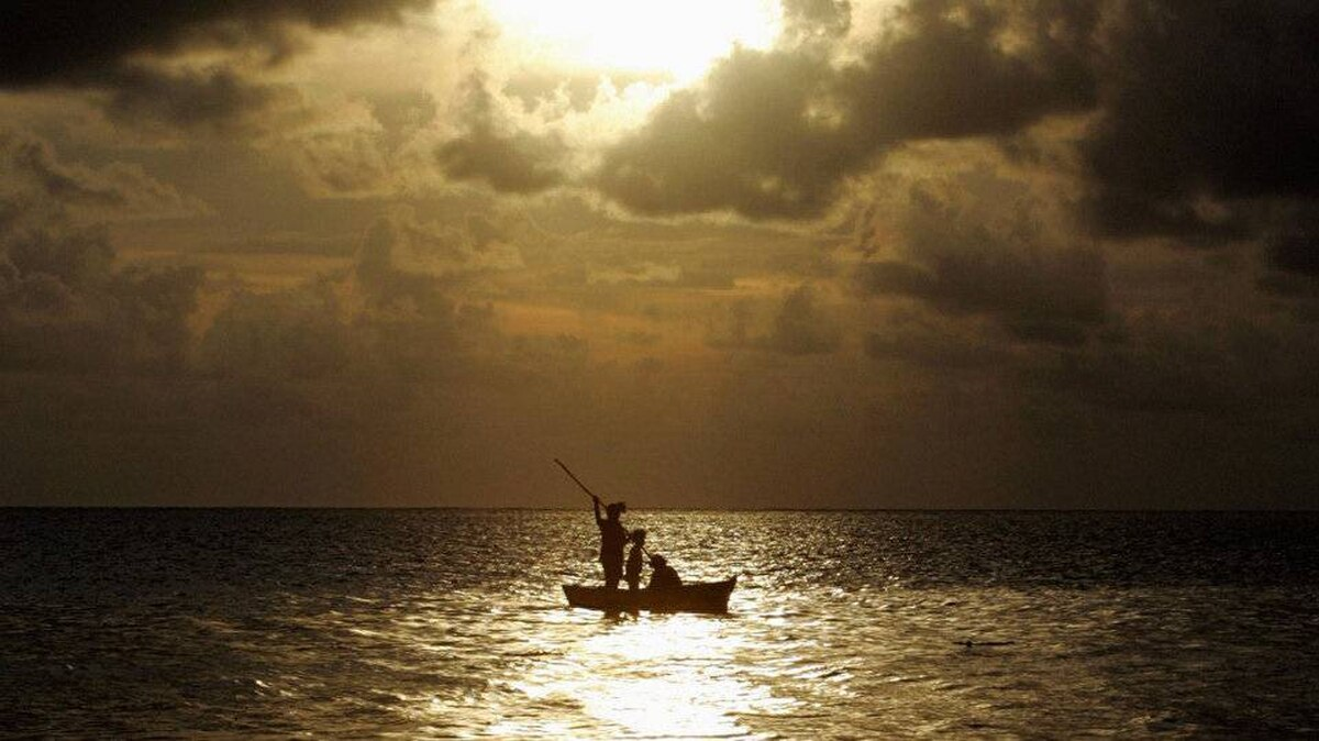 A fisherman and two children row across the harbour in front of Suva as evening approaches.