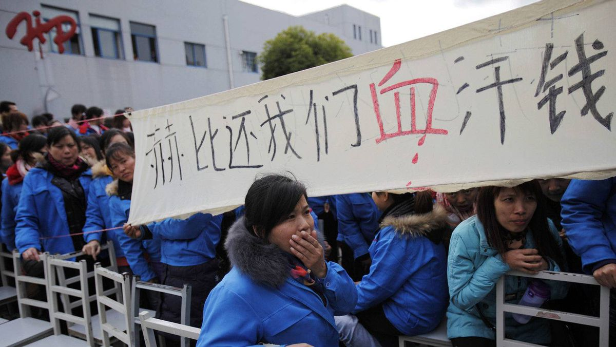Workers on strike hold a protest sign at the entrance gate of the Hi-P International factory in suburban Shanghai. The workers have lodged petitions demanding compensation and scuffled with police after blocking the shipment of heavy equipment.
