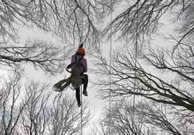 A participant clambers on a rope during a regional tourism competition among school students in a forest in Stavropol, Russia.