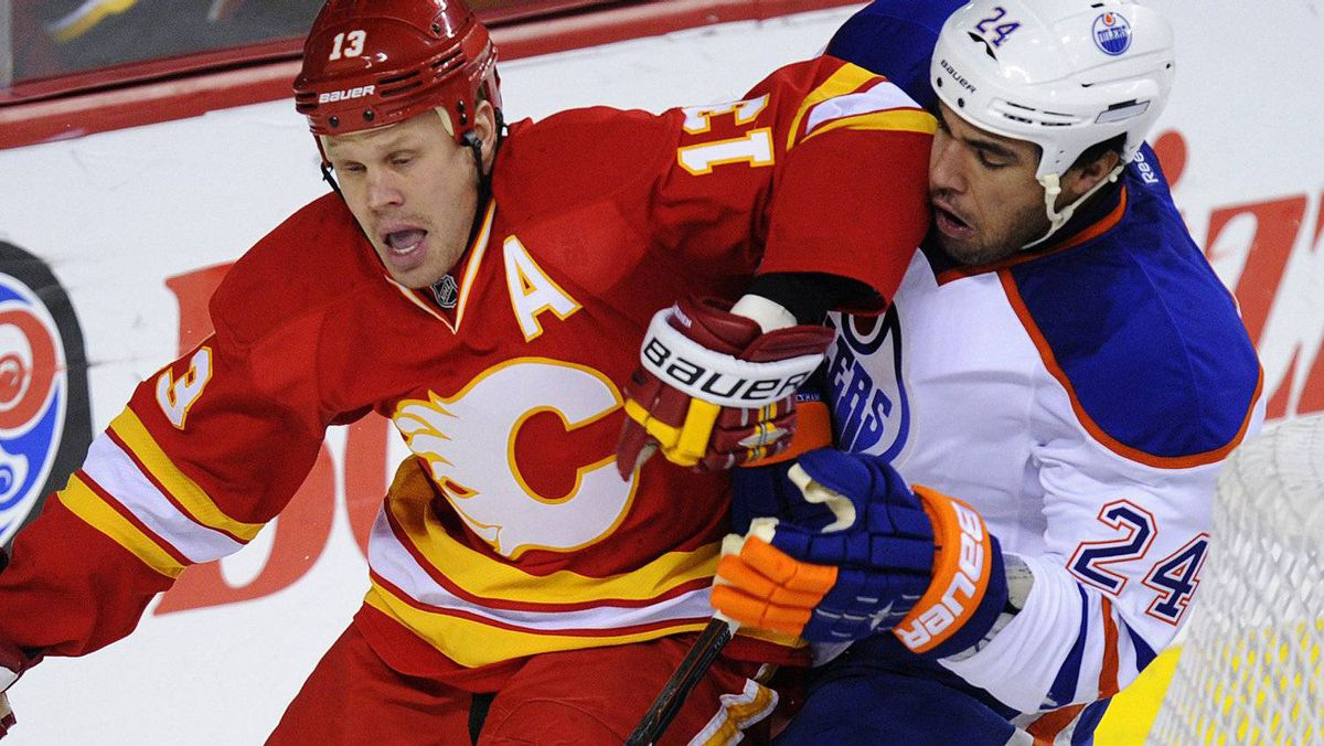 Calgary Flames' Olli Jokinen (L) tries to get away from Edmonton Oilers' Theo Peckham during the first period of their NHL hockey game in Calgary, Alberta, December 10, 2011. The Flames won 3-0. REUTERS/Todd Korol