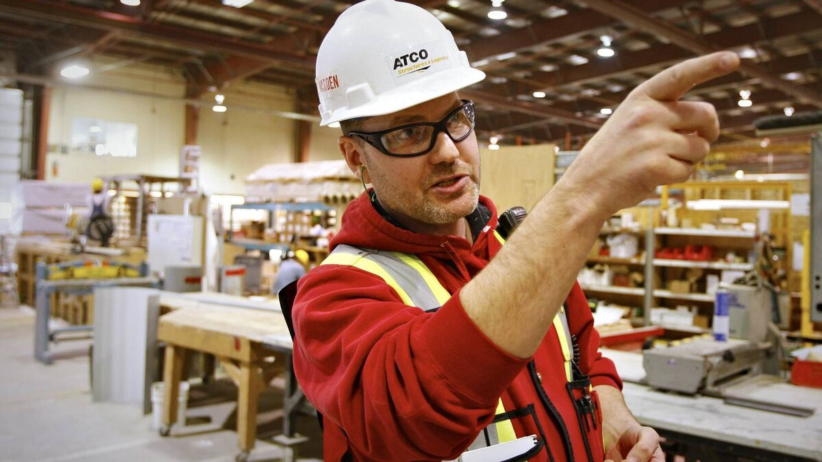 General foreman Dave Cook directs construction tradesmen as they build portable housing for oil sands workers at the Atco Structures facility in Calgary.