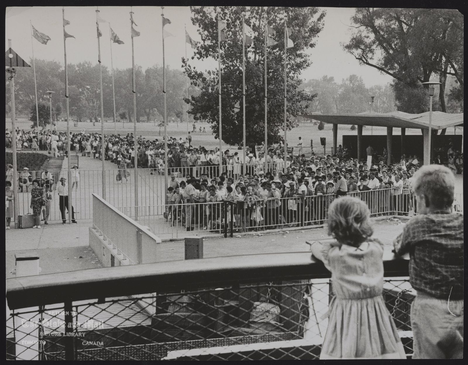 CENTRE ISLAND Multiple lineups for cooling voyages home across Toronto Bay extended almost as far as the lakefront beaches on Centre Island from the passenger loading areas at docks, [July 1, 1963]. From rail of ferry, girl and boy who were early in queues during evening look back at thousands waiting in heat for next boat.