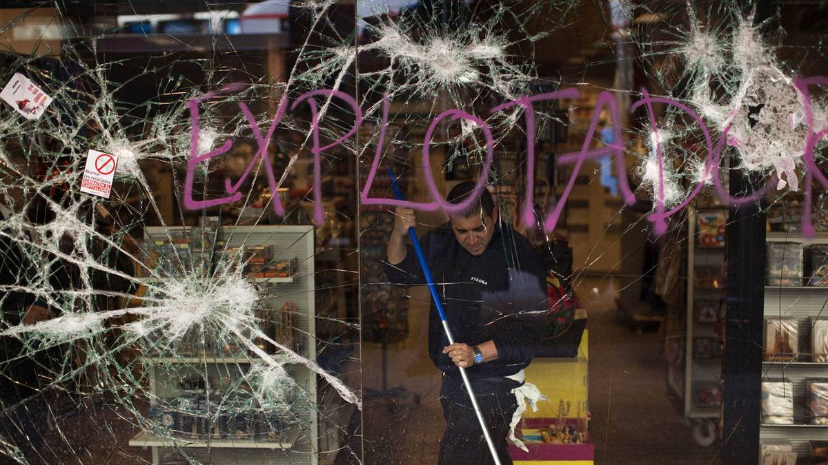 A worker cleans a shop stormed by demostrators following clashes between police and protesters after an anti-austerity general strike in Barcelona, Spain, Friday, March 30, 2012.