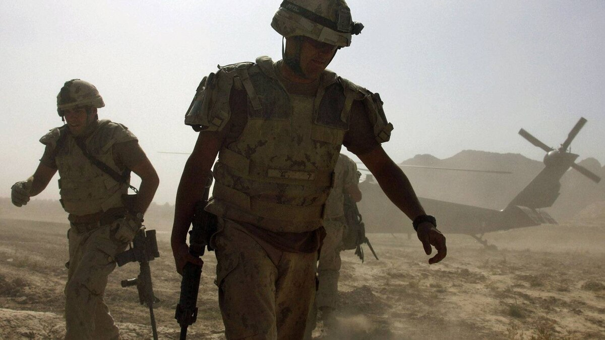 Canadian troops turn away from dust kicked up by a U.S. helicopter taking off in the Panjwaii district of Kandahar province, Afghanistan, on Sept. 24, 2009.