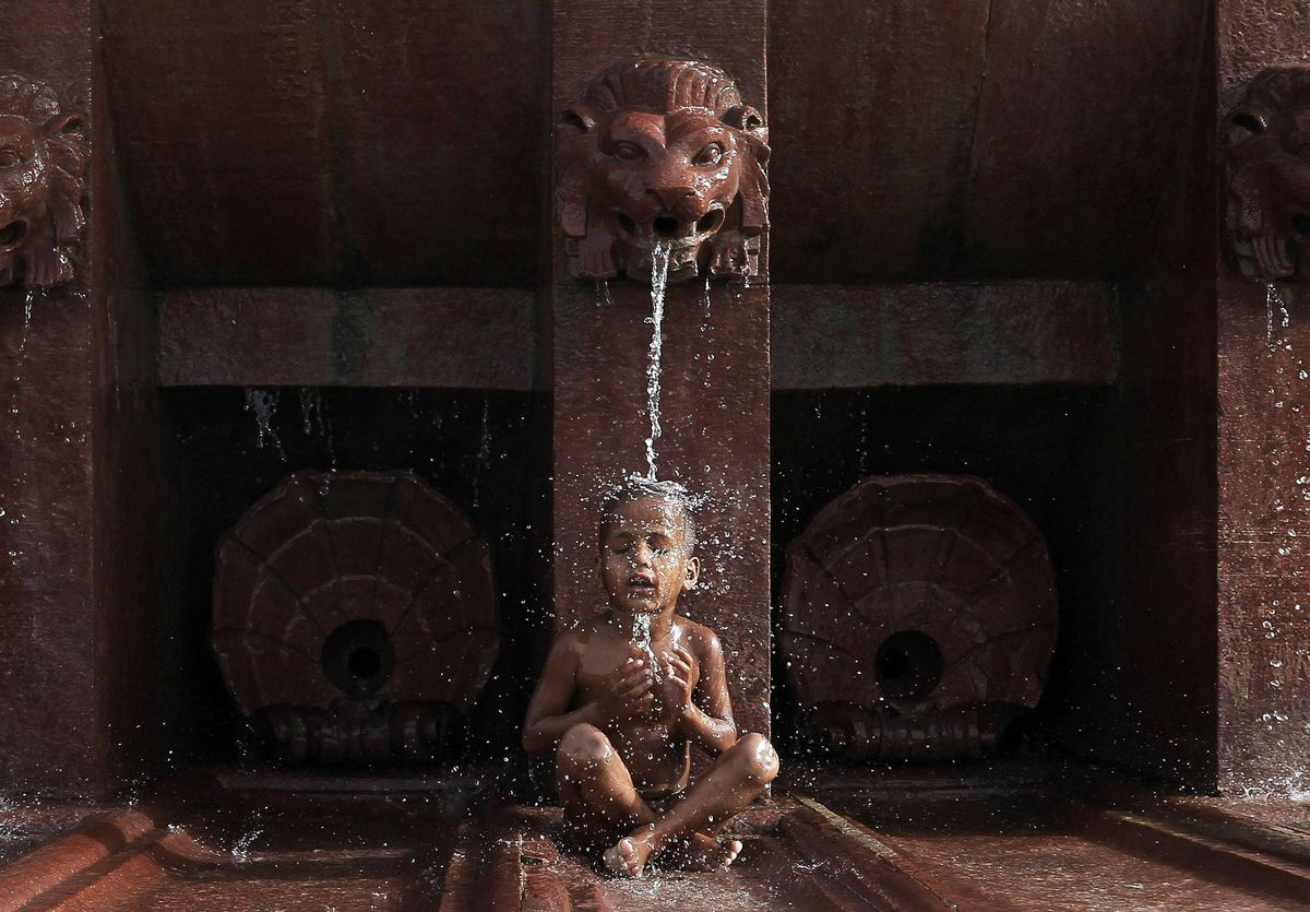 A boy cools himself off as he sits under a fountain on a hot summer day in New Delhi, India. Temperatures in New Delhi on Thursday reached 45 degrees Celsius according to information posted on India's metrological department website.