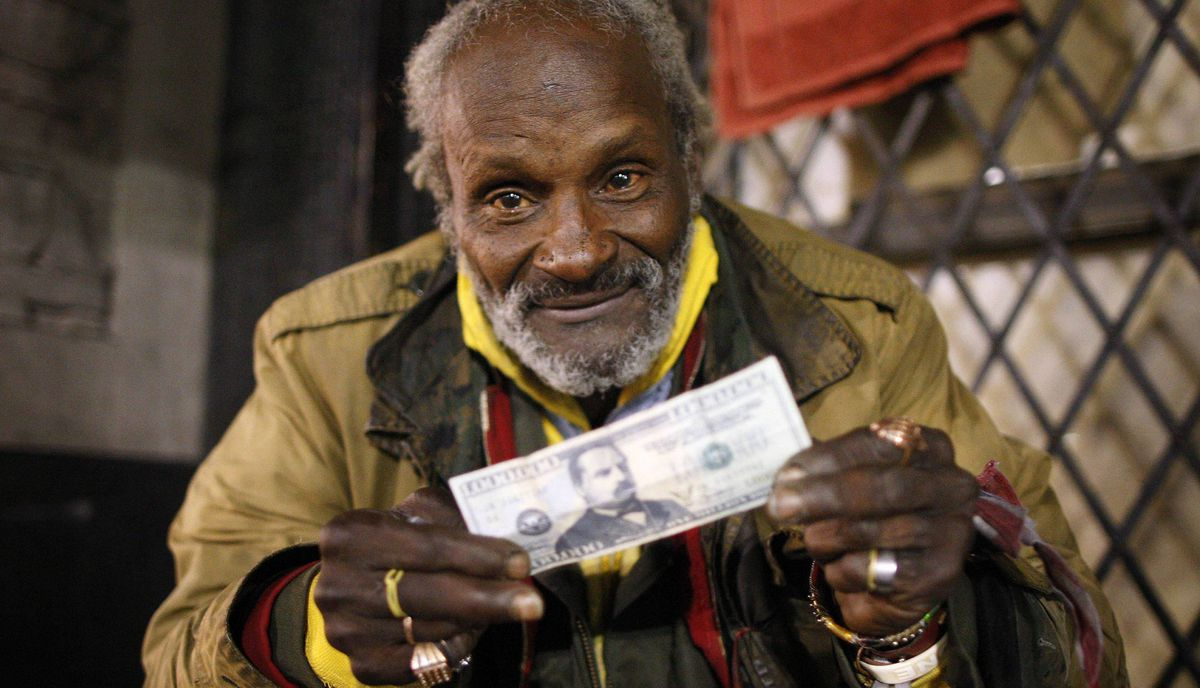 Richard McFarthing, a homeless man who sleeps on Hollywood Boulevard, shows off his play money in Hollywood, California late February 20, 2012.