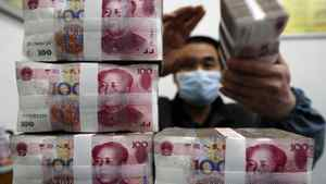 An employee counts Renminbi banknotes at a branch of Bank Of China in Changzhi, Shanxi province.