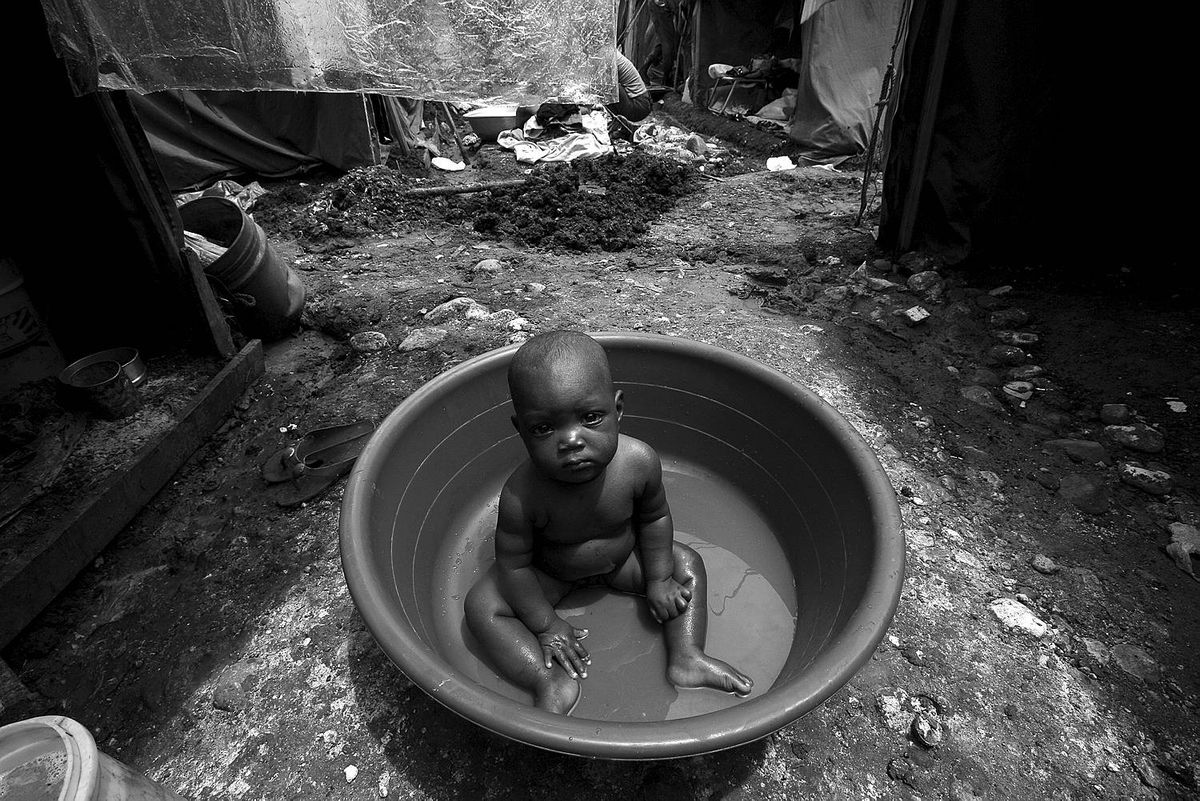 Jacmel, June 25/2010 - A baby sits in a tub in between the old army tents being used by some 1000 families in the displaced person camp of Pinchinat in Jacmel, Haiti, six months after people were located there during the emergency faze following the earthquake. Relocating the homeless people living there and at the many other sites in Jacmel continues to be a problem.
