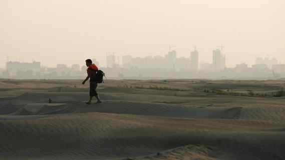 A man walks on a river shoal, which appeared after the water level of the Yangtze River declined, as the city of Wuhan is seen in the background, in Wuhan, Hubei province May 26, 2011. The worst drought to hit central China in half a century has brought water levels in some of the country's biggest hydropower producing regions to critical levels and could exacerbate electricity shortages over the summer.