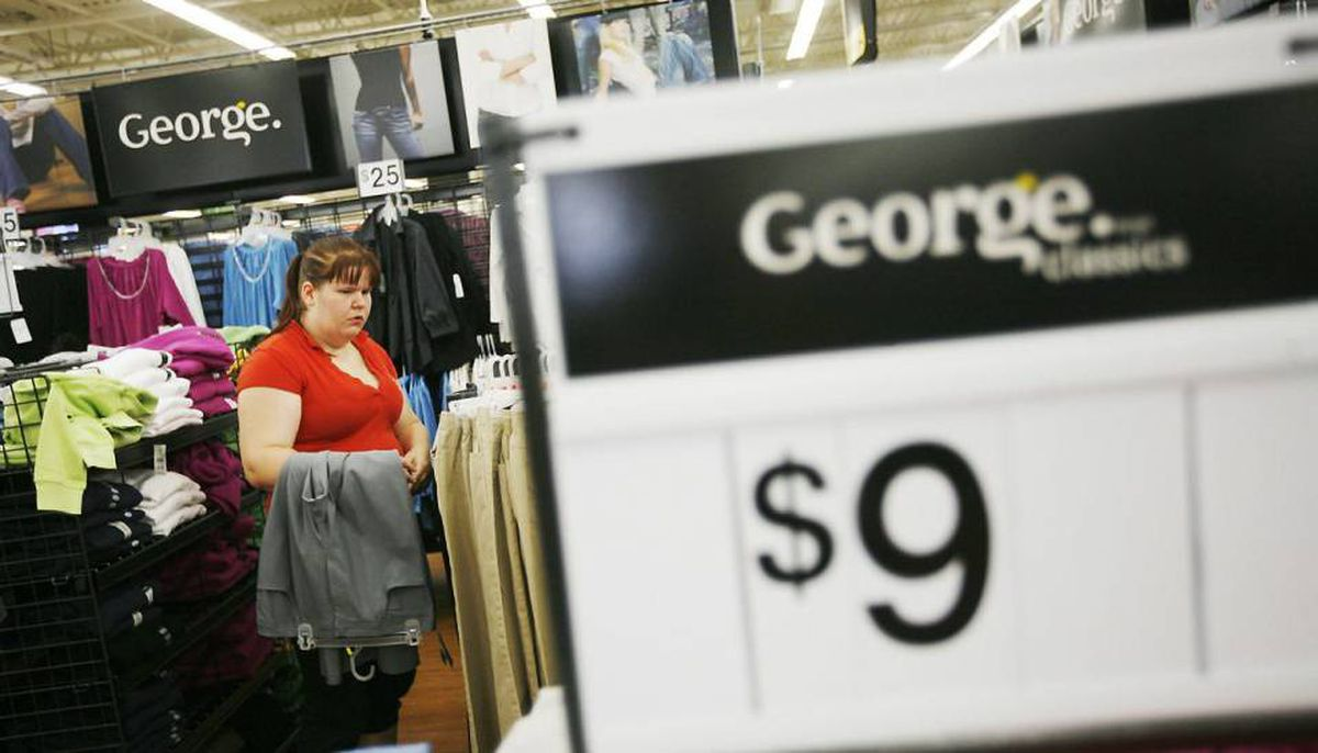 A shopper looks through racks of George clothing at a Wal-Mart in Toronto