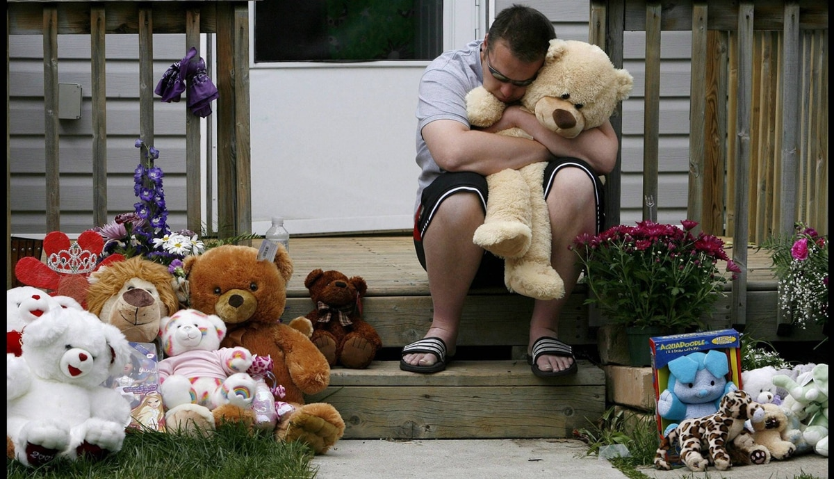 "James Goris partner of Victoria ""Tori"" Stafford's mother Tara McDonald hugs a bear left at their home as Tara speaks to the media, Friday, May 22, 2009 in Woodstock, Ontario."