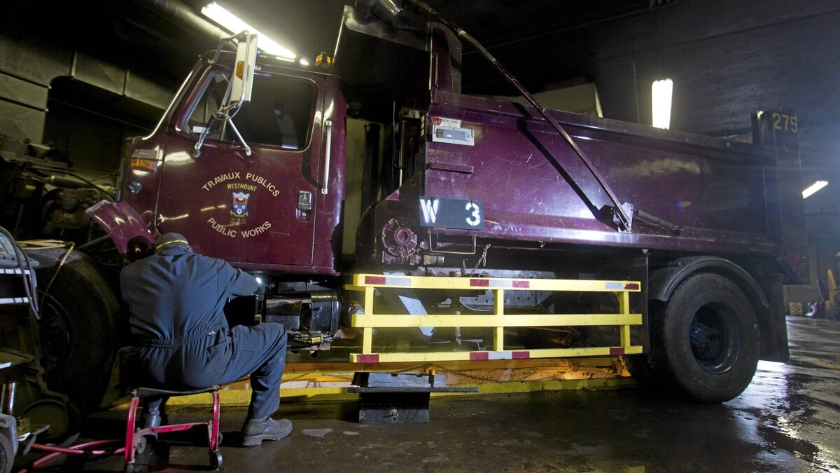 A Public Works' mechanic works on a dump truck which has been retrofitted with side guards, in their Westmount, Quebec garage on November 29, 2011.
