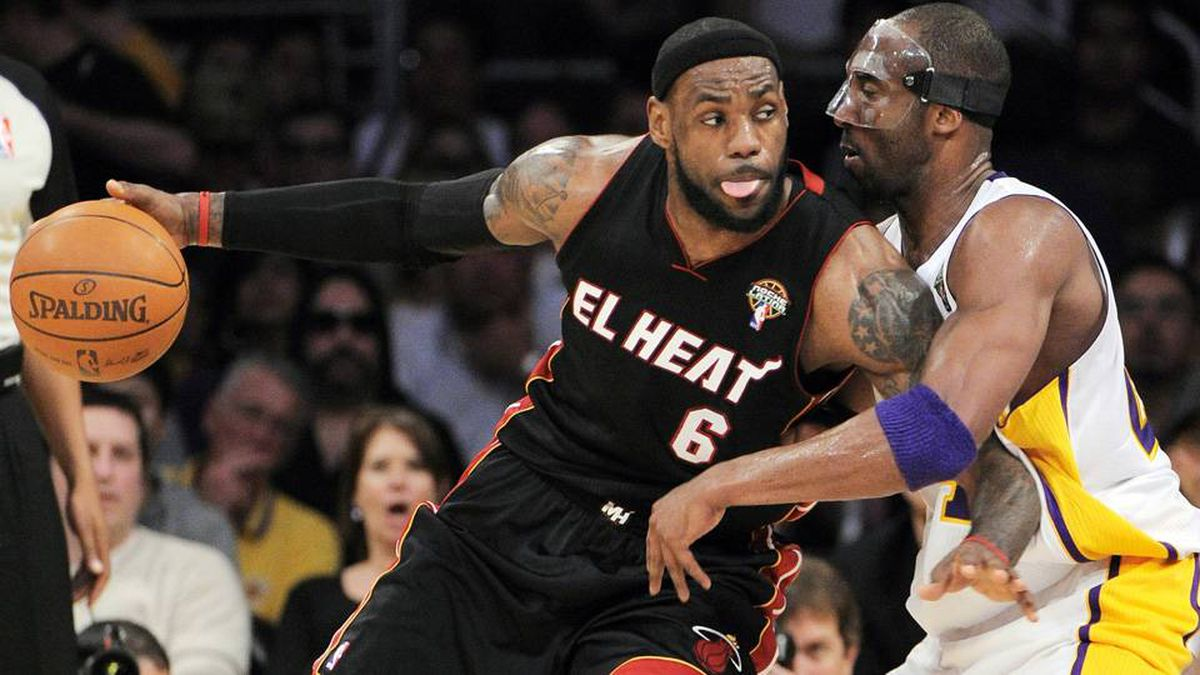 Miami Heat forward LeBron James (6) backs down on Los Angeles Lakers guard Kobe Bryant during the first half of their NBA basketball game in Los Angeles.