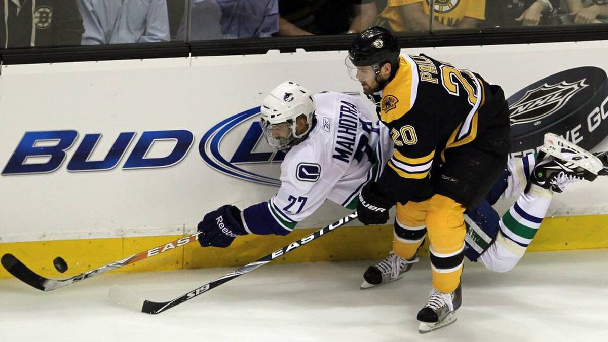 Vancouver Canucks centre Manny Malhotra, left, is checked by Boston Bruins left wing Daniel Paille.