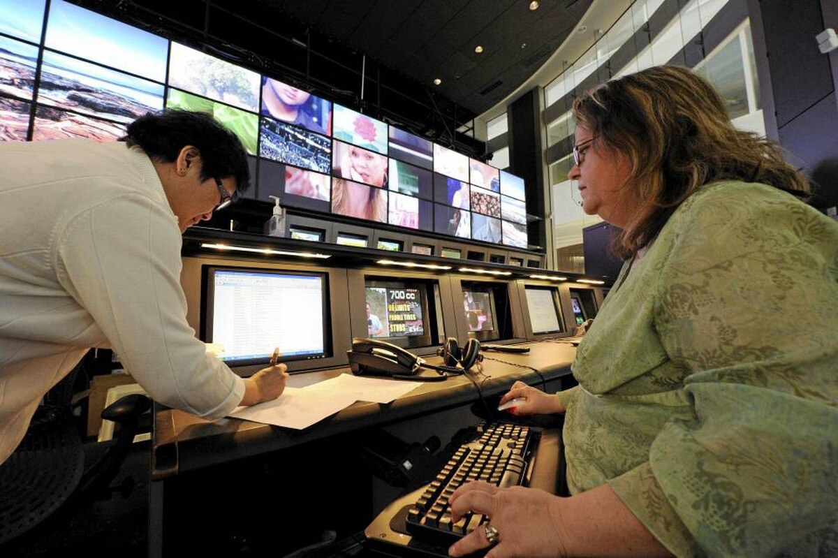 Supervisor Cindy Gravatt (R) and traffic co-ordinator Carina Basan work in the Shaw Communications' master control room in Calgary. Some analysts are questioning its deal for CanWest's TV assets. Todd Korol/REUTERS