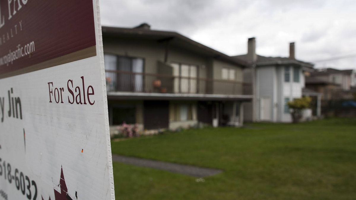 A for sale sign hangs in the front yard of a property in Burnaby, British Columbia, Monday, April 16, 2012.