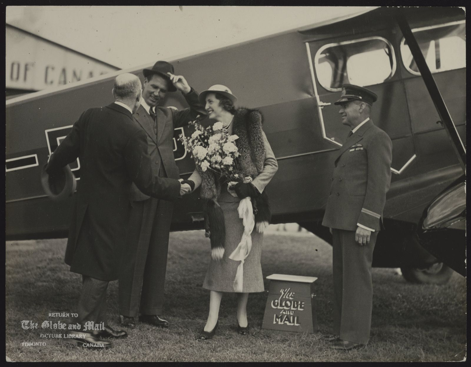 GLOBE & MAIL AIRPLANE Bill Wright shaking hands with Mrs. C. George McCullaugh, McCullagh lifting his hat, during christening of 'the flying newsroom'.