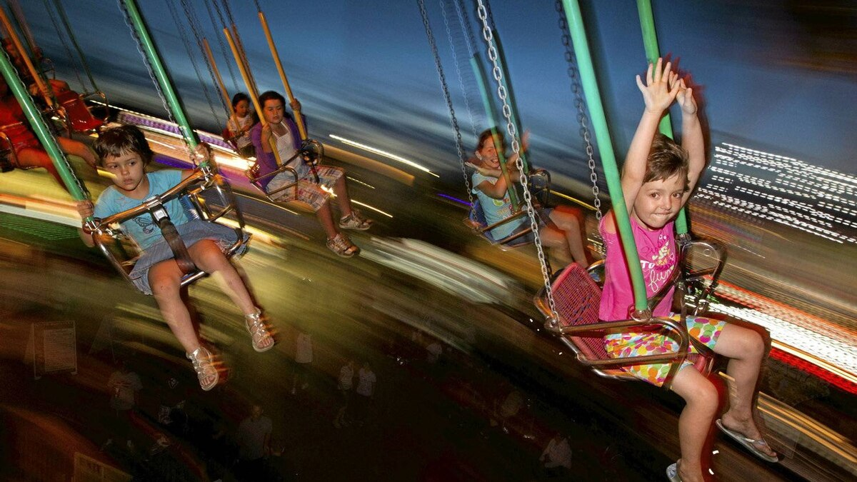 Maria Crudu, 6, far right with hands up, enjoys the Wave Swinger at the Pacific National Exhibition in Vancouver, Aug. 20, 2011.