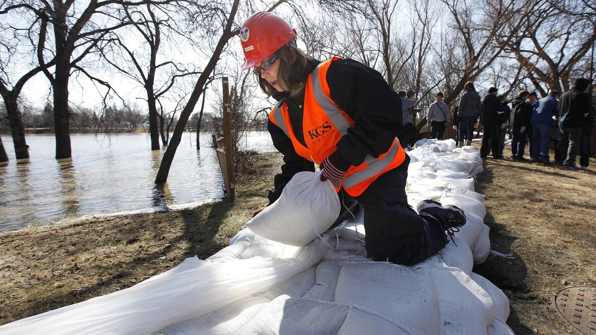 Melanie Schultz has taken a few days off work to build a dike to protect her home from the rising Red River in Winnipeg's north side on April 14, 2011. About 350 students volunteered in Winnipeg's north end to get sandbagging done in vulnerable areas.