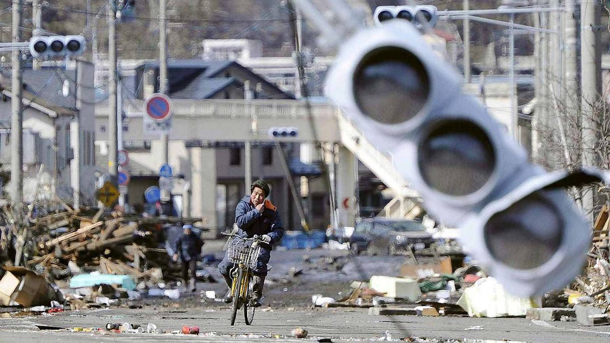 A man rides a bicycle through a debris-strewn street in Miyako, Iwate Prefecture in northeastern Japan March 12, 2011.