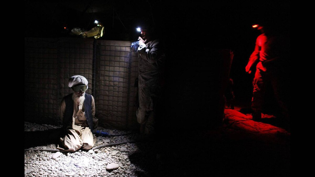 An Afghan man is detained by U.S. Marines from the First Battalion, Eighth Marines Bravo Company at their base in Talibjan after a battle against Taliban insurgents in Musa Qala district in southern Afghanistan's Helmand province, November 7, 2010.