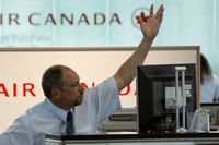 An Air Canada employee gestures for the next passenger at the check-in counter at Pearson International Airport in Toronto
